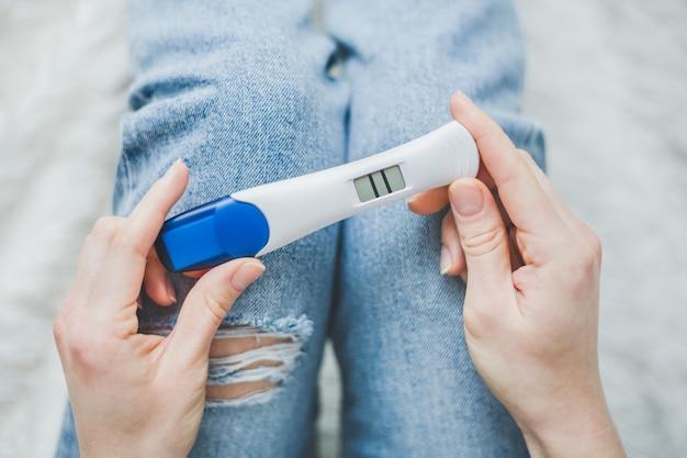 Mujer mirando en prueba de embarazo positiva