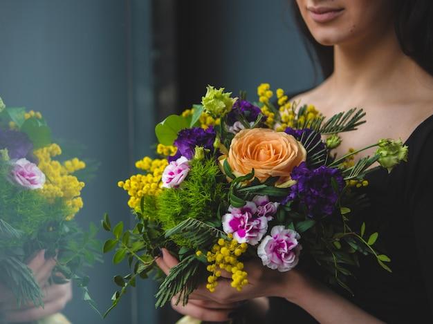 Una mujer mirando a un ramo de flores muy colorido frente a la ventana