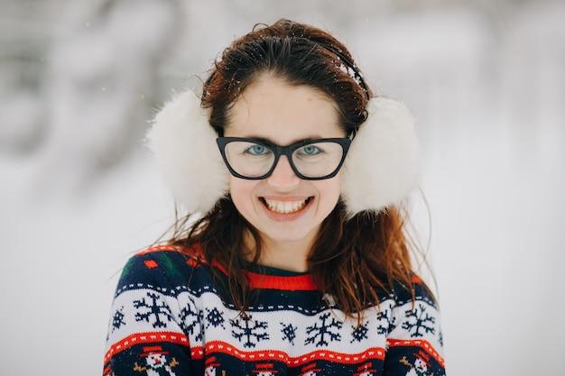 Mujer mirando y sonriendo. retrato de invierno de joven hermosa con orejeras, suéter posando en el parque cubierto de nieve.