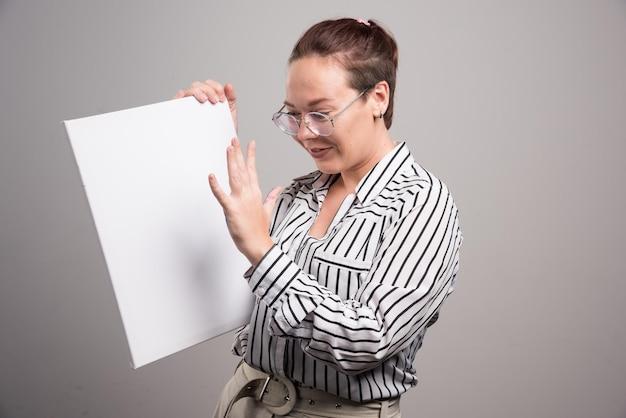 Mujer mirando su lienzo blanco vacío sobre gris