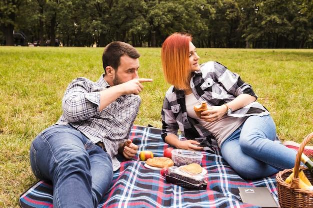 Mujer mirando a su novio apuntando a algo que disfruta de un picnic en el parque
