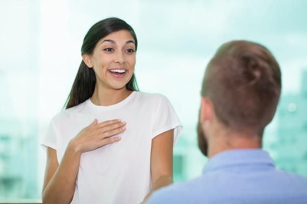 Una mujer mirando a su novio excitado con alegría