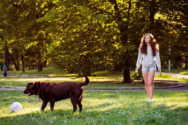 Mujer mirando a su perro jugando con la pelota en el parque