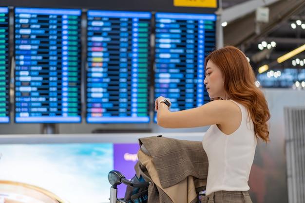 Mujer mirando su reloj inteligente con tablero de información de vuelo en el aeropuerto