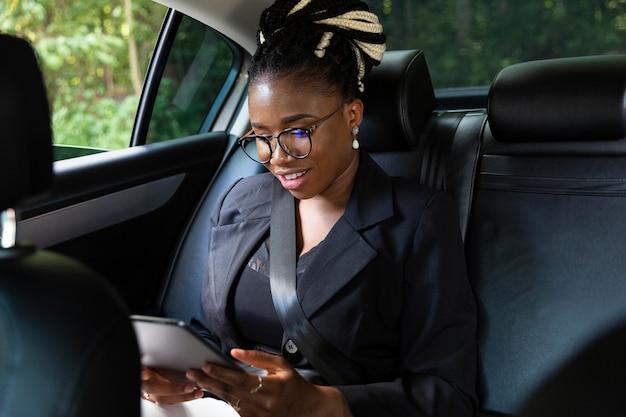 Mujer mirando tablet mientras está en el asiento trasero de su coche