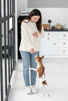 Mujer mirando el teléfono inteligente y darle golosinas a su perro