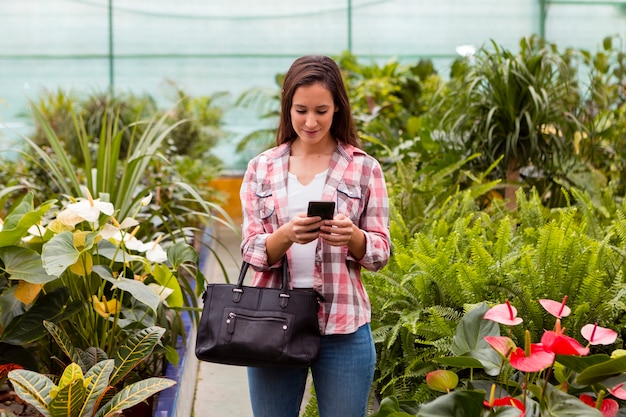 Mujer mirando el teléfono en invernadero