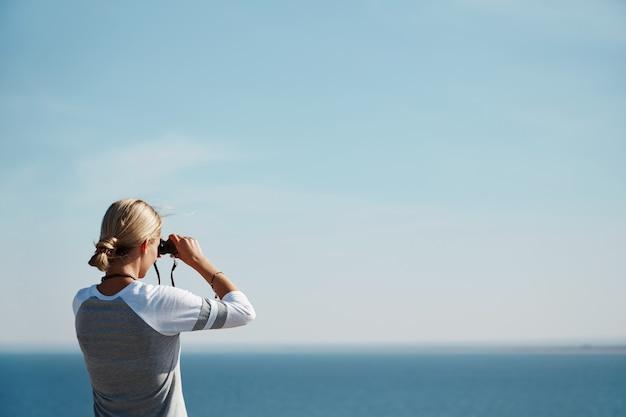 Mujer mirando a través de binoculares