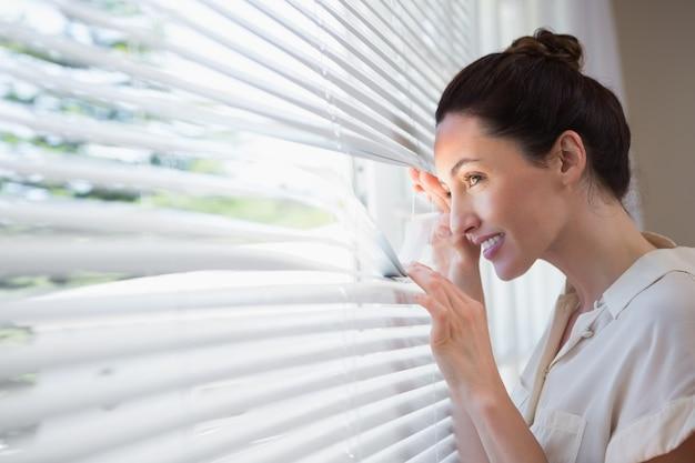 Mujer mirando a través de las persianas