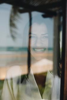 Mujer mirando por la ventana de su habitación de hotel