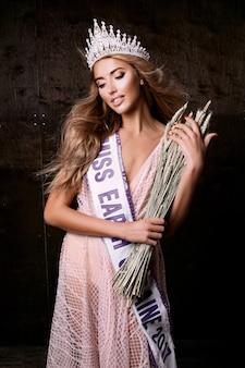 Mujer de miss tierra con corona, cinta y espiguillas de trigo. concurso de moda, bella modelo posando