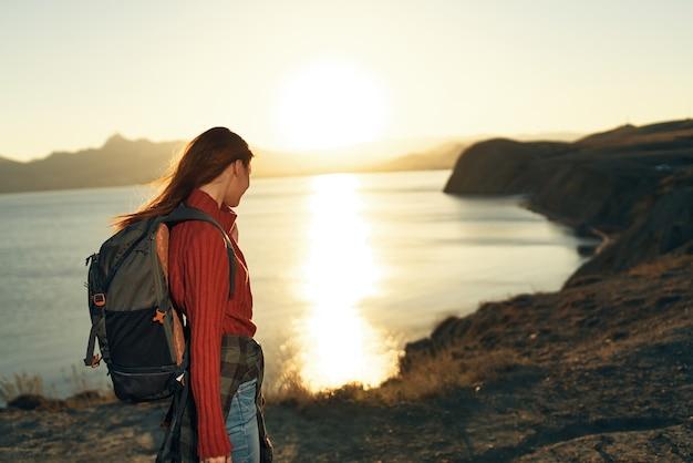 Mujer con mochila al aire libre y montañas rocosas viajan libertad de aire fresco