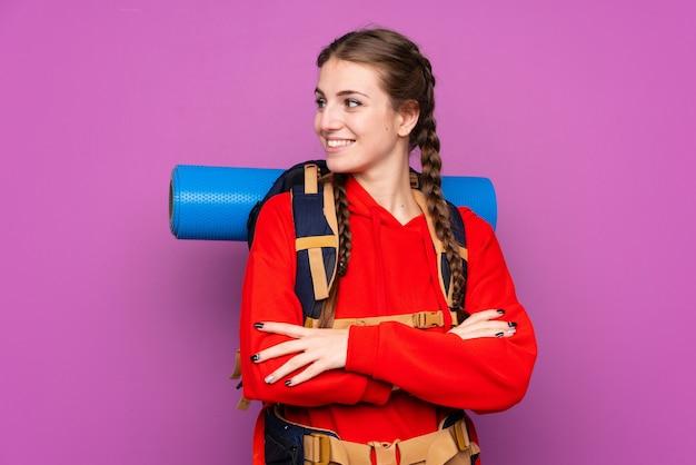 Mujer con mochila de alpinista sobre pared aislada