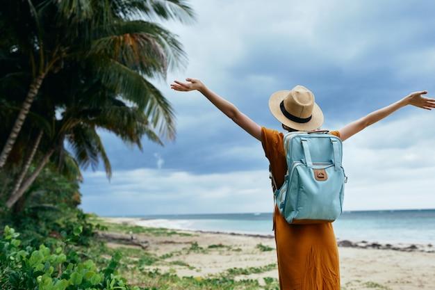 Mujer con una mochila azul en un vestido amarillo y sombrero camina por la arena con palmeras