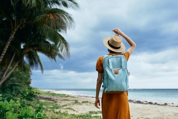 Mujer con una mochila azul en un vestido amarillo y sombrero camina a lo largo del océano a lo largo de la arena con palmeras
