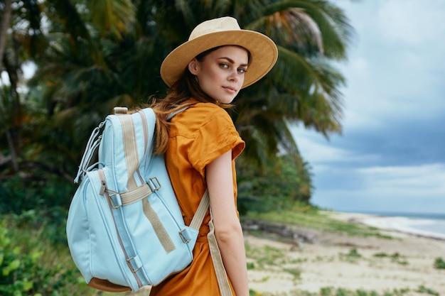 Una mujer con una mochila azul con un vestido amarillo y un sombrero camina por el océano a lo largo de la arena con palmeras