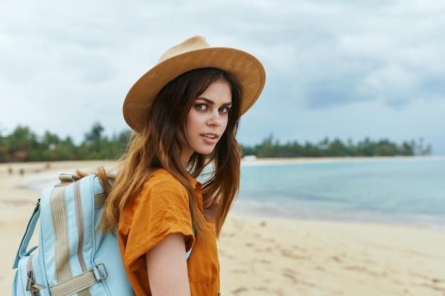 Una mujer con una mochila azul con un vestido amarillo y un sombrero camina por el océano a lo largo de la arena