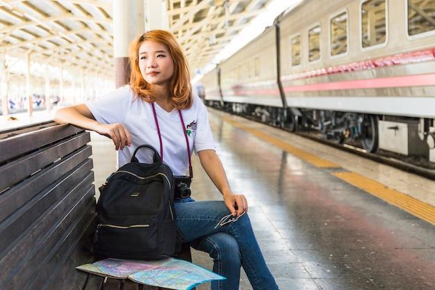 Mujer, con, mochila, y, cámara, en, banco, en, depósito