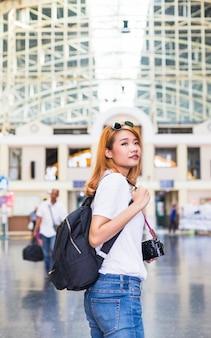 Mujer con mochila y cámara en estación de tren