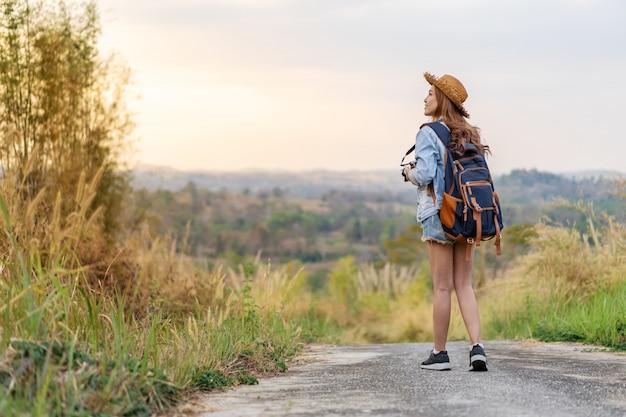 Mujer con mochila caminando en el sendero en la naturaleza