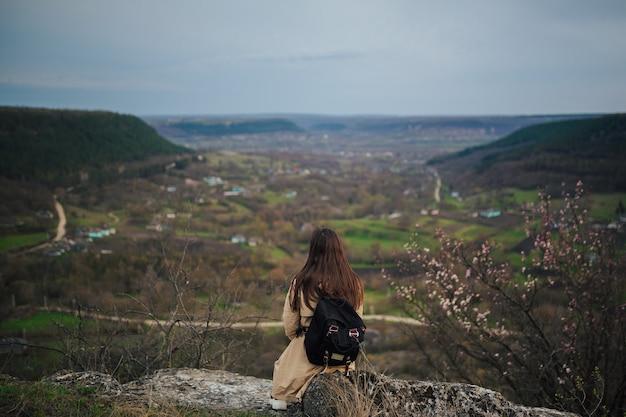 Mujer con mochila en la cima de una montaña vista posterior