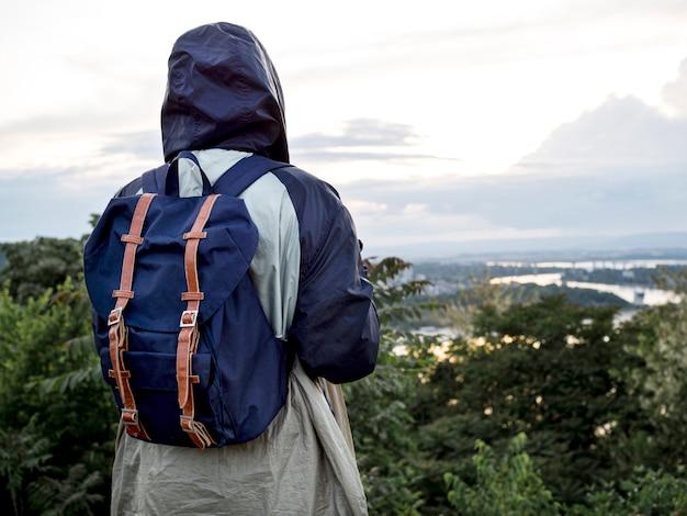 Mujer con mochila en la cima de la montaña