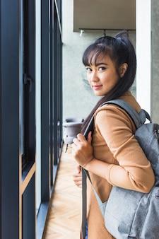 Mujer con mochila en jersey beige.