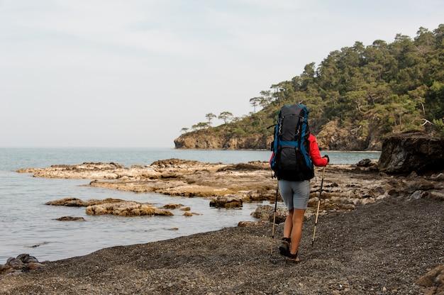 Mujer con mochila de senderismo en la costa del mar