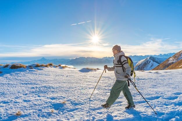 Mujer mochilero trekking en la nieve en los alpes.