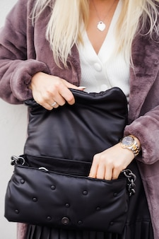 Mujer de moda en abrigo de piel marrón abrió bolso de cuero negro y está buscando algo. foto