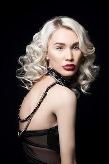 Mujer de moda de belleza con joyas en sus manos, cabello ondulado.
