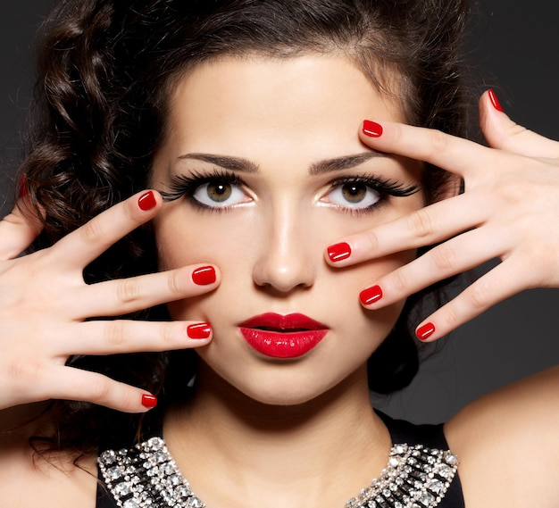 Mujer de moda de belleza con uñas rojas, labios y maquillaje de ojos dorados - en pared negra