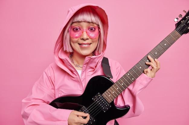 Mujer de moda con cabello rosado finge actuar en el escenario toca música rock and roll usa gafas de sol en forma de corazón y anorak posa en el interior contra la pared rosada. solista talentosa
