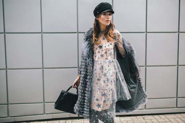 Mujer de moda caminando en la ciudad en abrigo de piel cálido y vestido de fiesta, accesorios de temporada de invierno