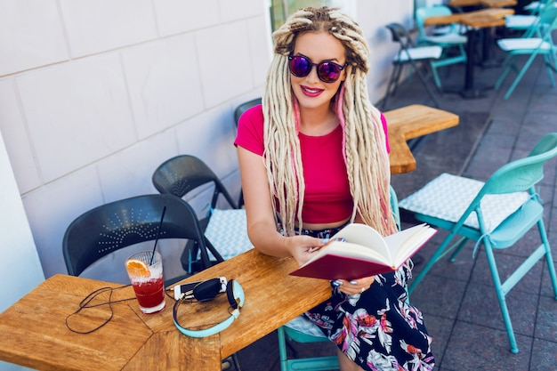 Mujer de moda elegante con rastas blancas en gafas de sol sosteniendo el cuaderno y pasando su tiempo libre en un restaurante moderno. batido fresco y auriculares en la mesa.
