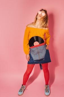 Mujer de moda de estilo retro con vinilo vintage sobre fondo rosa