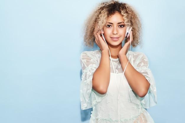 Mujer de moda feliz con peinado afro rubio sonriendo y escuchando música en auriculares