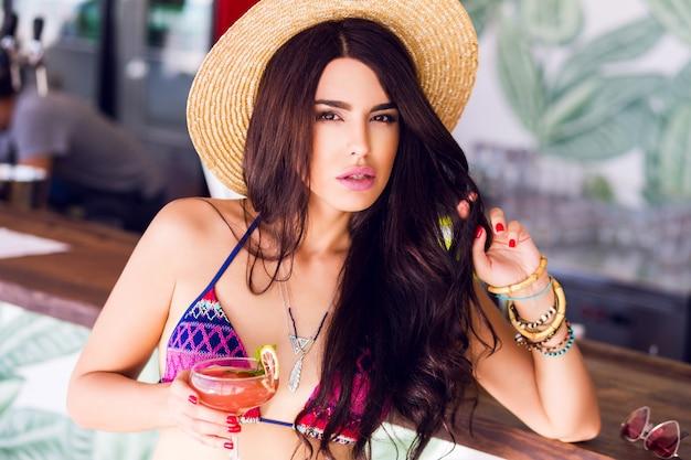 La mujer de moda en gafas de sol rosadas brillantes del corazón bebe el cóctel fresco de la fresa en el bar de la playa