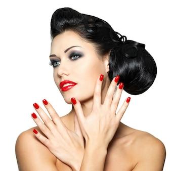 Mujer de moda hermosa con labios rojos, uñas y peinado creativo