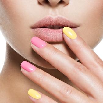 Mujer de moda con hermosas uñas multicolores
