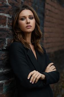 Mujer de moda joven de cabello castaño con bello rostro en abrigo clásico negro con cuello abierto de pie en pose con cruzado en el pecho manos brazos en la calle de la ciudad con pared de loft de tela de ladrillo rojo