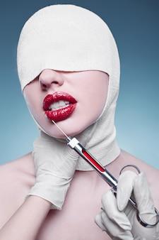 Mujer de moda joven con cabeza vendada e inyector