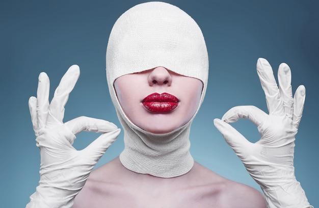 Mujer de moda joven con cabeza vendada y manos de enfermera
