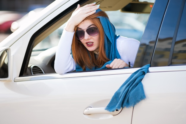 Mujer de moda joven conductor ha atascado el pañuelo en las puertas del vehículo y está tirando de él.
