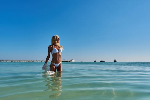 Mujer de moda joven de pie en el agua en la playa