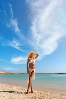 Mujer de moda joven de pie cerca del agua en la playa
