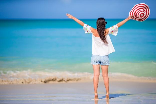 Mujer de moda joven con sombrero en la playa