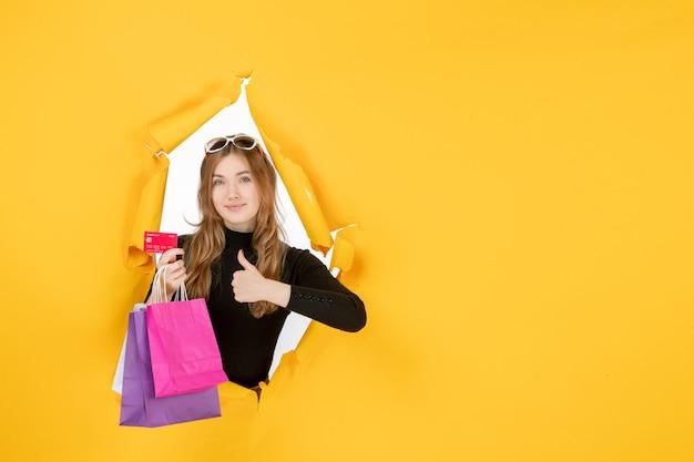 Mujer de moda joven sosteniendo bolsas de la compra y tarjeta de crédito a través del agujero de papel rasgado en la pared