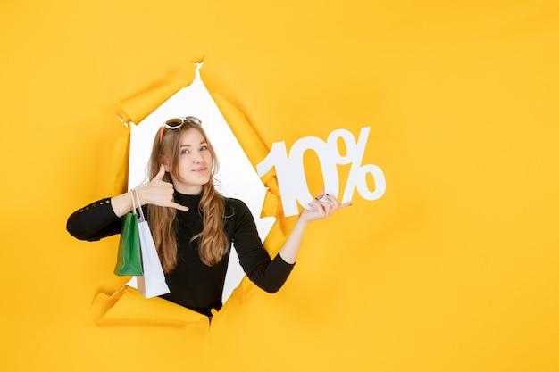 Mujer de moda joven sosteniendo bolsas de compras y porcentaje de descuento a través del agujero de papel rasgado en la pared