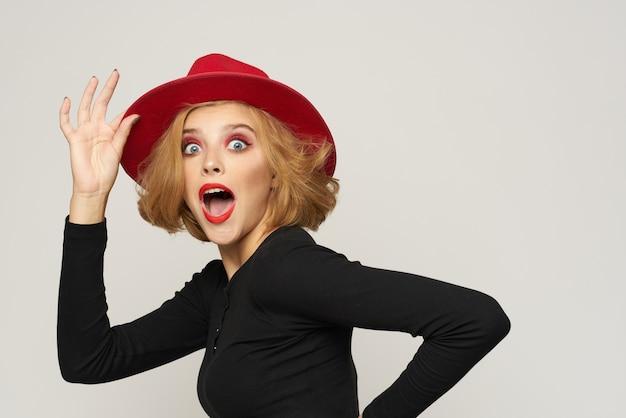 Mujer de moda en labios rojos blusa negra sombrero rojo recortada vista espacio ligero emociones.